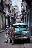 Two men leaning against a vintage car, Old Havana, Havanna, Cuba