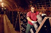 Man turning bottles, Cava Cellar methode champenoise, Codorniu, Sant Sadurni d'Anola, Catalonia, Spain