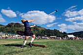 Man with kilt throwing a sledge hammer, Glenfinnan Highland Games, Invernesshire, Scotland, Great Britain, Europe