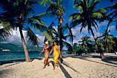Two women walking along the beach at Cayo Levantado, Bahia de Samana, Dominican Republic, Caribbean