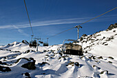 Chair lift in front of snowy mountainside, Ischgl, Samnaun, Tyrol, Austria, Europe