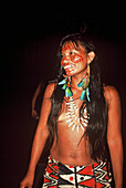 Portrait of young woman with feather decorations and facial painting, Native South American Tarianos, Amazonas, Brazil