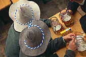 Two Men sitting on ale-bench with beer, Oktoberfest, Munich