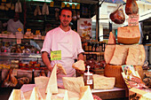 Man selling Parmesan cheese, Weekly market at Intra, Lago Maggiore, Piemont, Italy
