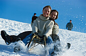 Young couple sledging down a slope, Winter sport