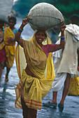 Laughing woman carrying a sack, Muzaffarpur, Bihar, India, Asia