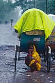 Woman hiding behind rickshaw, monsoon, Muzaffarpur, Bihar, India