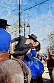 Man kissing woman on horseback, Feria del Caballo, Jerez de la Frontera, Province of Cadiz, Andalusia, Spain