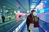 Couple kissing on a moving walkway, Munich Airport, Munich, Germany