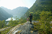 Father with daughter on the rocks above Geiranger Fjord, More og Romsdal, Norway