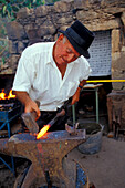 Blacksmith at the amboss, hammering iron, Canarian tradition, San Nicolas de Tolentino, Gran Canaria, Canary Islands, Spain