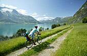 Woman with child on a bicycle, Lake Stryn, Sogn og Fjordane, Norway