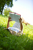 Young Woman reading book on lawn