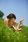 Young Woman reading book on lawn, Young Woman lying in meadow and reading a book, Bavaria