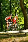 Couple riding fitness bicycles on forest track, Bavaria, Germany