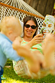 Woman relaxing in a hammock in the garden, reading a magazine, small boy standing nect to the hammock, relaxation