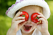 Young girl with tomatos on her eyes, garden