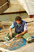 Fishermen in harbour, working on their net cala figuera, south, Mallorca, balearic islands, spain