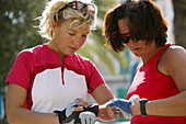 Women regarding their heart beat monitor, in cycling outfit, Majorca, Balearic Islands, Spain