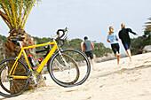 Three people on a cycle tour on the beach of cala santanyi, Majorca, Balearic Islands, Spain