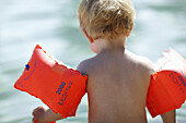 Boy 2 years, wearing water wings, Amersee Lake, Upper Bavaria, Germany