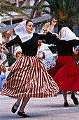 Two young girls in traditinal costume dancing to folklore music, Majorca, Spain
