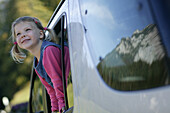 Young girl looking out the car window, Young girl looking out of the car window, Alpenstrasse, Reiteralpe, Ramsau, Germany, Junges Maedchen blickt aus Autofenster, Alpenstrasse, Spiegelung Reiteralpe, Ramsau, D