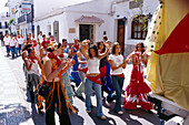 People in a procesion on a sunlit street, Romeria de San Isidro, Nerja, Costa del Sol, Malaga province, Andalusia, Spain, Europe