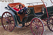 Two young women having a rest on a carriage, Romeria de San Isidro, Nerja, Costa del Sol, Malaga province, Andalusia, Spain, Europe