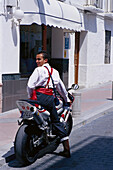 Young man in traditional costumes on a scooter, Romeria de San Isidro, Nerja, Costa del Sol, Malaga province, Andalusia, Spain, Europe