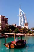 A boat on the canal and the Burj al Arab hotel, Dubai, United Arab Emirates, Middle East, Asia
