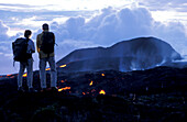 Two people watching glowing lava at Piton Kapor volcano, Ille de la Réunion, Indian Ocean