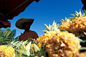 Local man selling pineapple on a market stall, Market in St. Paul, La Réunion, Indian Ocean