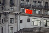 The chinese flag in front of grey houses, Shanghai, China, Asia