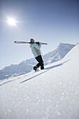 Woman going with skis uphill, Kuehtai, Skifahrerin, Hohe Mut und Gaiskogel im Hintergrund, Kuehtai, Tyrol, Austria