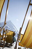 Woman relaxing in deck chair, Hohe Mut in backround, Kuehtai, Tyrol, Austria