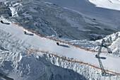 View to ski lift, Skiers in a ski lift, Schwarzen Schneid, Rettenbachferner, Soelden, Oetztal, Austria