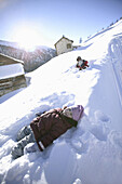 Two children playing in deep snow, Livigno, Italy