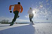 Young couple walking through powder snow