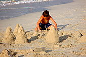 Boy building a sand castle on the beach, Dubai, UAE, United Arab Emirates, Middle East, Asia