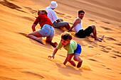 Playing children on a dune, Dubai, UAE, United Arab Emirates, Middle East, Asia