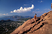 Woman hiking up Gran Cratere with view over Lipari, Vulcano, Aeolian Islands, Italy