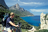 Man on a Vespa enjoying the views, Punta Pedra Longa, Baunei, Sardinia, Italy