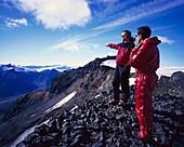 Men on mountainside looking at view, Brokarjoekull Glacier, Iceland