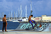 Boys with skateboard at a halfpipe at harbour, Port Olimpic, Barcelona, Spain, Europe