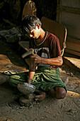young man hammering a metal bowl, Myanmar