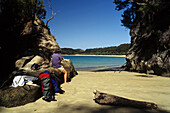 Hiker in a sunny bay, Abel Tasman Coast Track, Torrent Bay, Abel Tasman National Park, New Zealand, Oceania