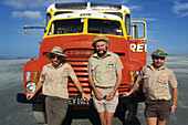 Three tour guides in front of truck at the coast of Tasman Sea, New Zealand, Oceania