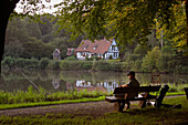 Angler sitting on a bench, Horn Bad-Meinberg, North Rhine-Westphalia, Germany