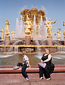 Visitors sitting in front of central fountain, All-Russian Exhibition Centre, Moscow, Russia
